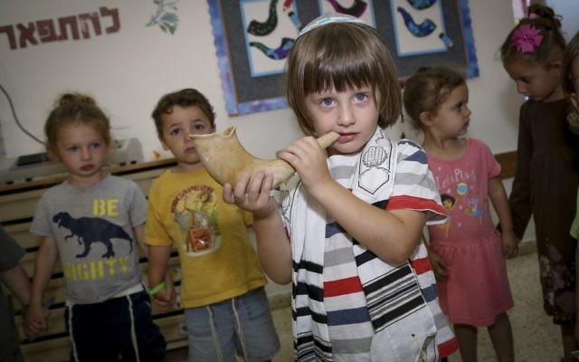 Un enfant israélien souffle dans un shofar dans un jardin d'enfants d'Efrat, dans le Gush Etzion, le 8 septembre 2016. Le shofar est principalement utilisé à Rosh Hashana, le nouvel an juif. (Crédit : Gershon Elinson/Flash90)