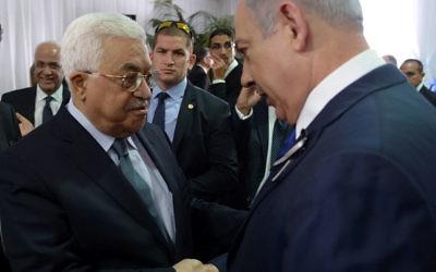 Le Premier ministre Benjamin Netanyahu et le président de l'Autorité palestinienne Mahmoud Abbas pendant les funérailles d'état du 9e président Shimon Peres, au cimetière du mont Herzl, à Jérusalem, le 30 septembre 2016. (Crédit : Amos Ben Gershom/GPO)