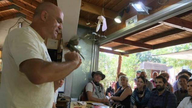 Amir Balaban présente un rossignol devant un groupe de participants à l'observatoire ornithologique de Jérusalem, le 14 septembre 2016. (Crédit : Jessica Steinberg/Times of Israel)
