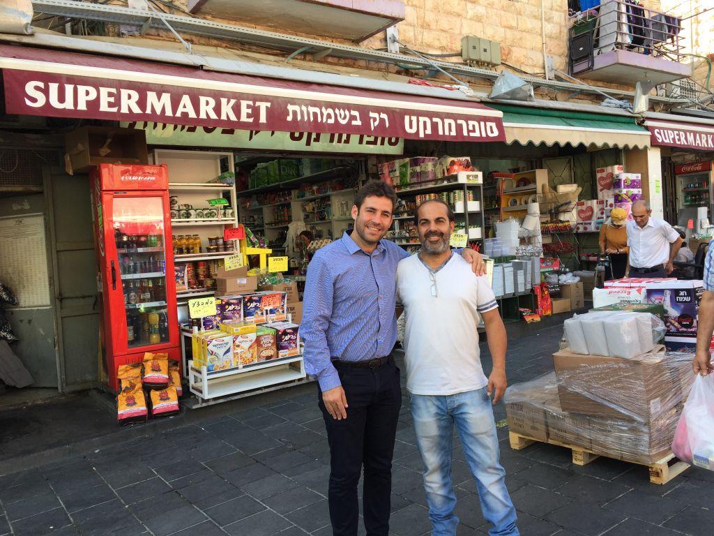 Ofer Berkovitch, vice maire de Jérusalem (à gauche), et le président du marché Mahane Yehuda Nino Peretz, devant le magasin de Peretz dans une rue non couverte du marché, en octobre 2016. (Crédit : Jessica Steinberg/Times of Israel)