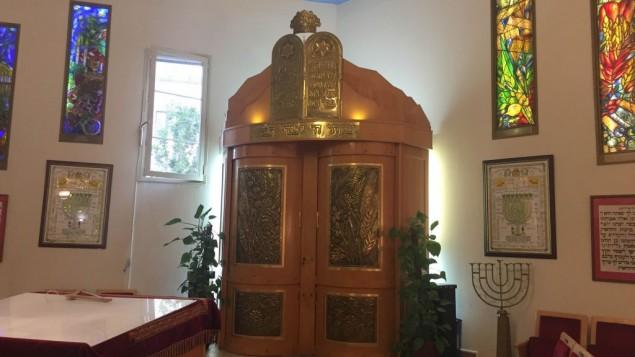 La grande salle de la synagogue d'Issy-les-Moulineaux, aux murs ornés de six vitraux, représentant des fêtes juives. (Crédits : Héloïse Fayet / Times of Israel)