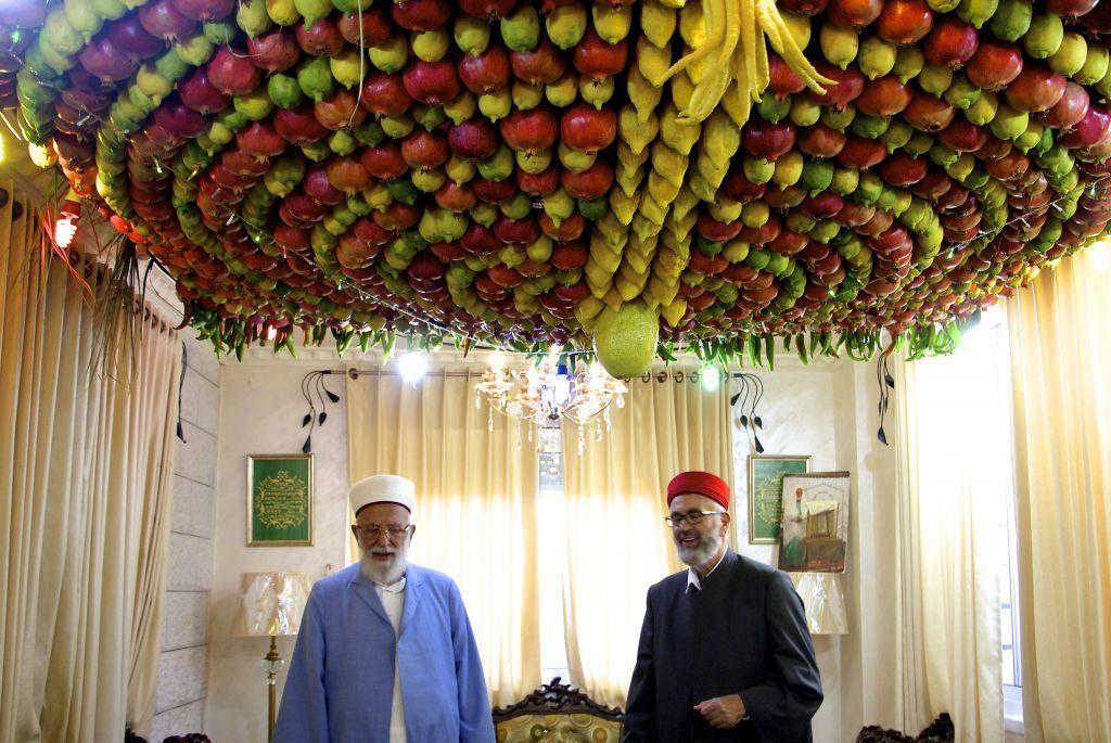 Le grand prêtre Samaritain, Abdullah Wassef Tawfiq, se tient avec son frère Husney Cohen dans son salon avec une « succah » fait maison à base de fruits frais pour la fête des Tabernacles ou Souccot, sur le mont Garizim près de la ville de Naplouse en Cisjordanie , le 18 Octobre, 2016 (Crédit : Dov Lieber / Times of Israel)