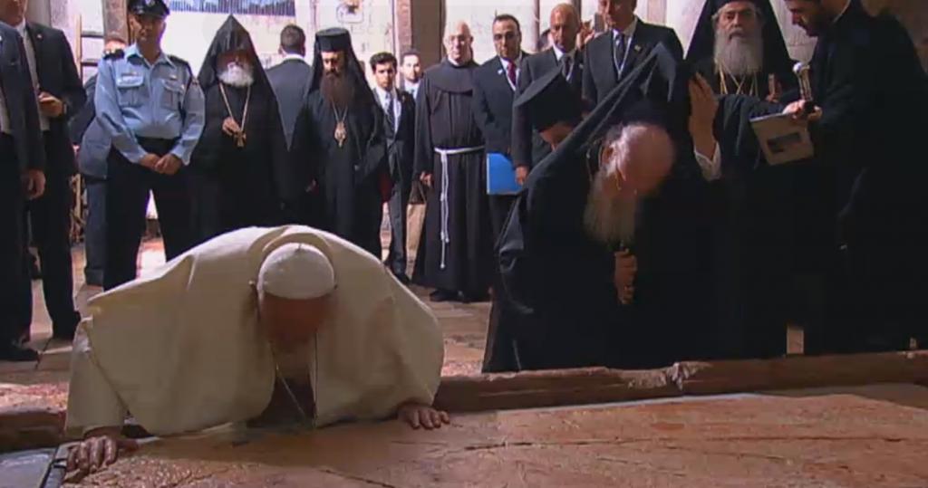 Le pape François et le patriarche Barthélémy embrassent la Pierre de l'Onction de l'église du Saint-Sépulcre, à Jérusalem, en 2014. (Crédit : capture d'écran GPO)