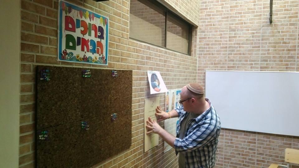 Rabbi Joshua Barton de Nashville, TN, qui a mené un groupe d'étudiants Hillel de Vanderbilt en 2015, en train de décorer les murs à Shirat Hayam (Crédit : Autorisation)