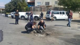 Les démineurs de la police sortent un morceau de la roquette tirée depuis la bande de Gaza qui a atterri sur une route de Sdérot, le 5 octobre 2016. (Crédit : police israélienne)