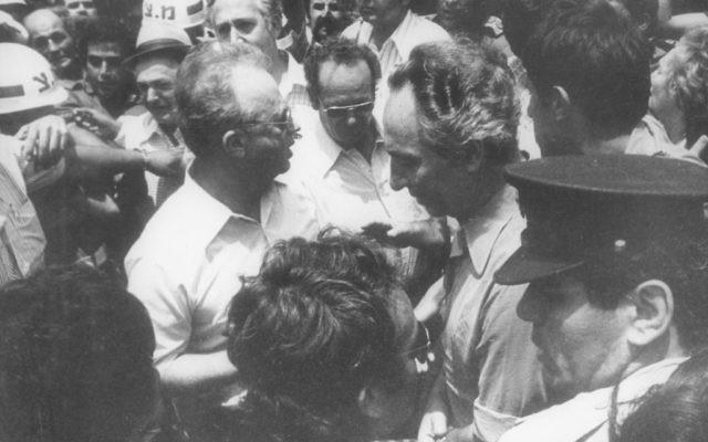 Shimon Peres, alors ministre de la Défense, et l'ancien Premier ministre Yitzhak Rabin, rencontrent les otages libérés d'Entebbe à leur atterrissage en Israël, le 4 juillet 1976. (Crédit : archives du ministère de la Défense)