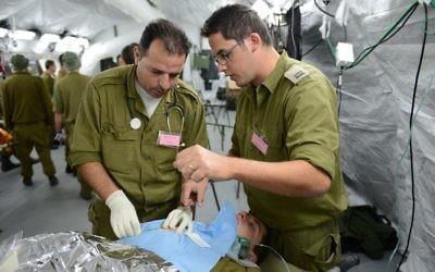"""Deux médecins militaires israéliens réalisent une """"chirurgie"""" pendant un exercice d'hôpital de campagne à Beit Naballah, dans le centre d'Israël, le 9 décembre 2013. (Crédit : unité des porte-paroles de l'armée israélienne)"""
