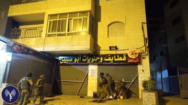 Les troupes israéliennes dans le village d'A-Ram, au nord de Jérusalem, scellent le magasin de bonbons possédé par la famille du terroriste qui a tué deux Israéliens dimanche matin à Jérusalem, le 11 octobre 2016. (Crédit : capture d'écran d'une vidéo fournie par l'unité des porte-paroles de l'armée israélienne)