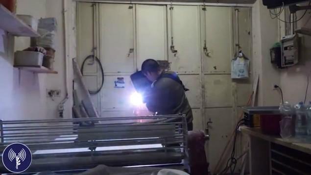 Un ingénieur de l'armée israélienne soude des barres de fer à l'entrée du magasin de bonbons possédé par la famille du terroriste qui a tué deux Israéliens dimanche matin à Jérusalem, dans le village d'A-Ram, au nord de Jérusalem, le 11 octobre 2016. (Crédit : capture d'écran d'une vidéo fournie par l'unité des porte-paroles de l'armée israélienne)