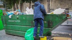 Un homme fouillant une poubelle dans le centre de Jérusalem. (Crédit : Nati Shohat / Flash90)