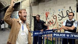 Yehudah Glick passe devant un policier en descendant du mont du Temple de la Vieille Ville de Jérusalem, le 10 octobre 2013. (Crédit : Sliman Khader/Flash90)