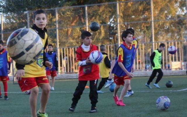 Des enfants juifs et arabes s'entrainent ensemble à Jérusalem, dans le cadre du programme Kick It Out pour éliminer le racisme dans le milieu du football. (Crédit : Yossi Zamir)