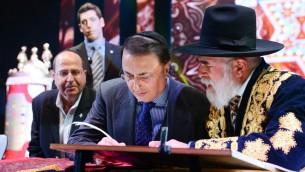Lev Leviev, au centre, écrit dans un rouleau de Torah avec le rabbin Eliyahu Yaakov, à droite, et Moshe Yaalon, alors ministre de la Défense, à Jérusalem, le 23 mars 2014. (Crédit : Israel Barddougo/Congrès mondial des juifs de Bukhara/JTA)
