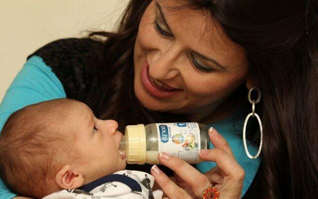 Une mère nourrit son enfant avec un lait maternisé Materna, le 28 février 2011. Illustration. (Crédit : Nati Shohat/Flash90)