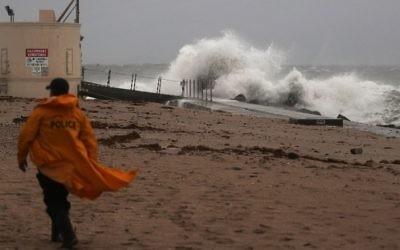 Un policier parcourt la plage tandis que les vagues s'écrasent sur la plage, avec l'arrivée de l'ouragan Matthew, à Singer Island, en Floride, le 6 octobre 2016. (Crédit : Joe Raedle/Getty Images/AFP)