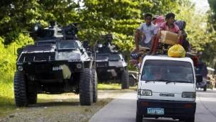 Des personnes conduisent près d'un véhicule de transport blindé (APC) à Kauran, Ampatuan, au sud des Philippines dans la Provicne de Maguindanao, le 24 décembre 2015. (Crédits : AFP PHOTO/MARK NAVALES)