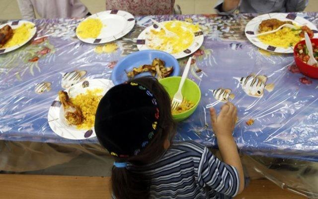 Un jeune garçon juif en train de manger au centre Yad Ezra V'Shulamit à Jérusalem, qui sert un déjeuner chaud tous les jours à plus de 1 200 enfants vivant sous le seuil de pauvreté, le 27 septembre 2011. Illustration. (Crédit : Uri Lenz/Flash90)