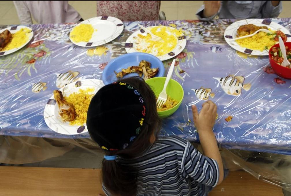 Un jeune garçon juif en train de manger au centre Yad Ezra V'Shulamit à Jérusalem, qui sert un déjeuner chaud tous les jours à plus de 1 200 enfants qui vivent sous le seuil de pauvreté, le 27 septembre 2011 (Crédit : Uri Lenz / FLASH90)