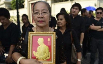 Une femme tient une représentation du Roi thaïlandais Bhumibol Adulyadej, dans la queue pour rendre hommage au Grand Palais à Bangkok le 14 octobre 2016 (Crédits : AFP/Munir Uz Zaman)