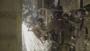Des soldats forcent les portes une imprimerie qui produisait, d'après l'armée israélienne, des affiches et d'autres documents de soutien au terrorisme, à A-Ram, en Cisjordanie, le 19 octobre 2016. (Crédit : unité des porte-paroles de l'armée israélienne)