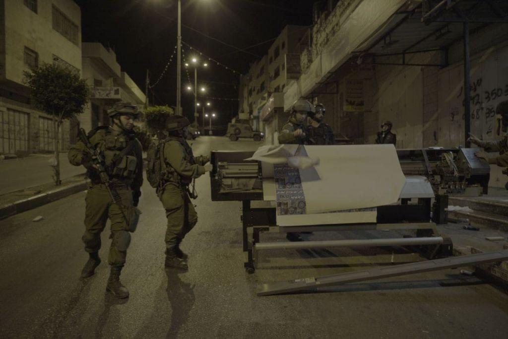 Des soldats saisissent du matériel dans une imprimerie qui produisait, d'après l'armée israélienne, des affiches et d'autres documents de soutien au terrorisme, à A-Ram, en Cisjordanie, le 19 octobre 2016. (Crédit : unité des porte-paroles de l'armée israélienne)