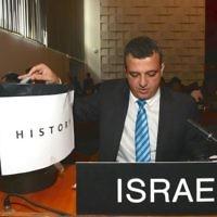 """L'ambassadeur israélien auprès de l'UNESCO, Carmel Shama-Hacohen, prend une copie de la résolution tout juste votée à l'UNESCO, et la met à la poubelle de """"l'histoire"""", le 26 octobre 2016. (Crédit : Erez Lichtfeld)"""