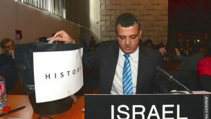 """L'ambassadeur israélien auprès de l'UNESCO, Carmel Shama-Hacohen, prend une copie de la résolution tout juste votée à l'UNESCO, et la met à la poubelle de """"l'histoire"""", le 26 octobre 2016. (Crédit : autorisation)"""