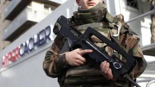 Un soldat français déployé devant la plaque commémorative du supermarché HyperCacher de Paris, le 4 janvier 2016. (Crédit : Thomas Samson/AFP)