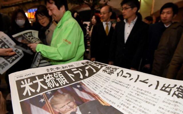 Un homme distribue des éditions supplémentaires des journaux annonçant la victoire de Donald Trump à l'élection présidentielle américaine à Tokyo, le 9 novembre 2016. (Crédit : AFP/Toru Yamanaka)
