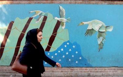 Une Iranienne voilée devant une fresque dessinée su le mur de l'ancienne ambassade américaine à Téhéran, le 9 novembre 2016. (Crédit : Atta Kenare/AFP)