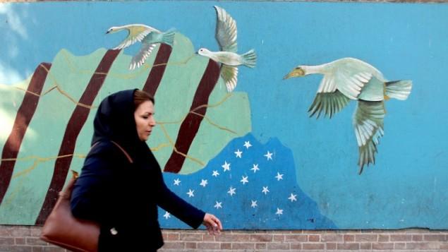 Une Iranienne passe devant une fresque dessinée su le mur de l'ancienne ambassade américaine à Téhéran, le 9 novembre 2016. (Crédit : AFP/Atta Kenare)