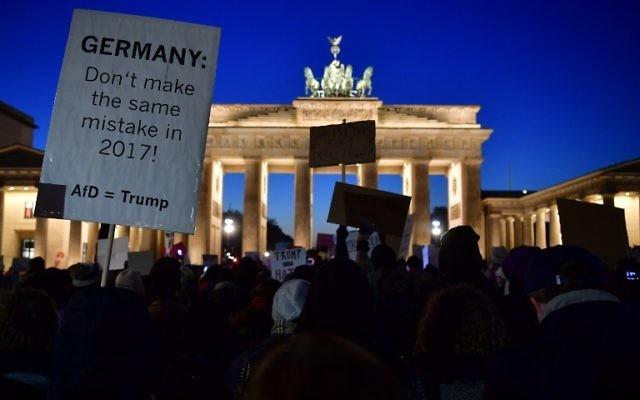 Des manifestants protestent contre l'élection de Donald Trump à la présidence des Etats-Unis à la porte de Brandebourg de Berlin, le 12 novembre 2016. (Crédit : AFP/ John MacDougall)