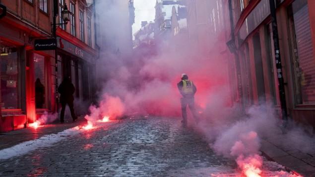 Des contremanifestants lancent des fumigènes contre la police alors qu'ils protestent contre le Mouvement de résistance nordique (NMR) dans le centre de Stockholm, en Suède, le 12 novembre 2016. (Crédit : AFP/Jonathan Nackstrand)