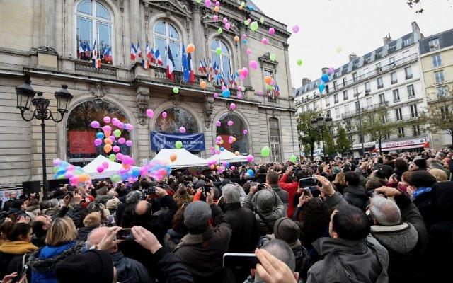 Les gens lancent des ballons devant la mairie du 11ème arrondissement de Paris, le 13 novembre 2016, pour marquer le premier anniversaire des attentats de Paris. (Crédit : AFP/ ALAIN JOCARD)