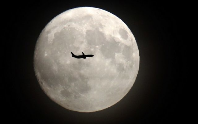 Un avion de ligne passe devant la Lune à son approche de l'aéroport d'Heathrow, à l'ouest de Londres, le 13 novembre 2016. (Crédit : AFP/Adrian Dennis)
