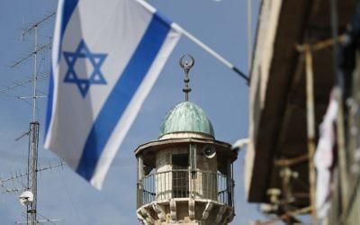 Un drapeau israélien devant un minaret d'une mosquée du quartier musulman de la Vieille Ville de Jérusalem, le 14 novembre 2016. (Crédit : Thomas Coex/AFP)