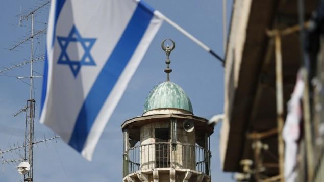 Un drapeau israélien devant un minaret d'une mosquée du quartier musulman de la Vieille Ville de Jérusalem, le 14 novembre 2016. (Crédit : AFP/Thomas Coex)