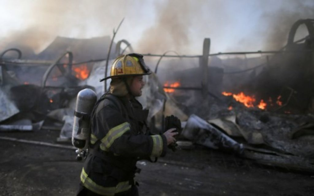 Des pompiers israéliens aident à éteindre un incendie dans la ville du nord de Haïfa le 24 novembre 2016. (Jack Guez / AFP)