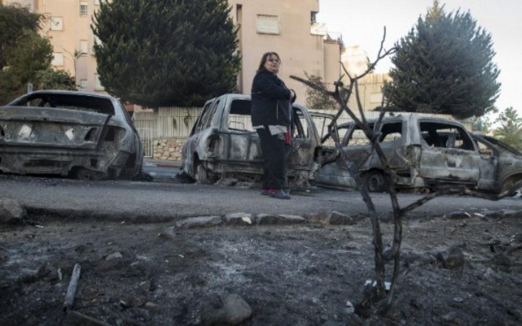 Une femme passe devant les voitures brûlées par les feux de forêt du 25 novembre 2016. (Crédits : AFP)