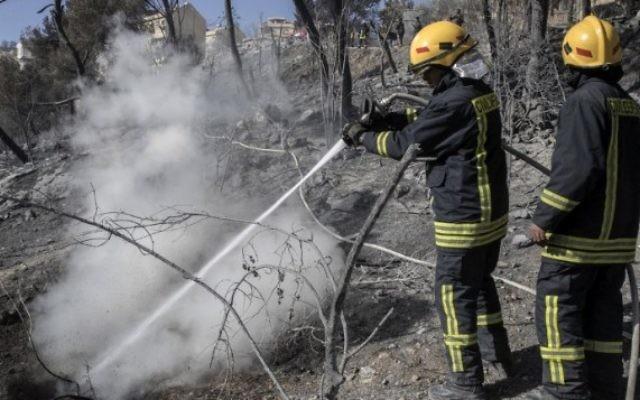 Des pompiers israéliens éteignent un incendie dans la ville du nord de Haïfa, le 24 novembre 2016. (Crédit : AFP/Jack Guez)