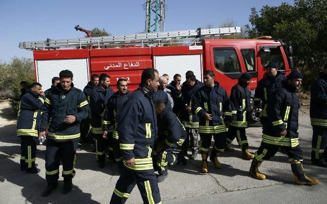 Les pompiers palestiniens arrivent à Nataf, près de Jérusalem, pour aider à éteindre un incendie dans la région, le 26 novembre 2016. (Crédit : Ahmad Gharabli/AFP)