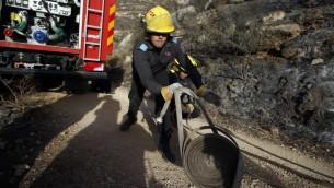 Un pompier israélien lutte contre le feu à Nataf, près de Jérusalem, pour aider à éteindre un incendie dans la région, le 26 novembre 2016. (Crédit : AFP/Ahmad Gharabli)