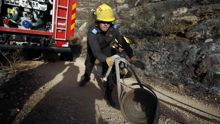 Un pompier israélien lutte contre le feu à Nataf, près de Jérusalem, pour aider à éteindre un incendie dans la région, le 26 novembre 2016. (Crédit : Ahmad Gharabli/AFP)