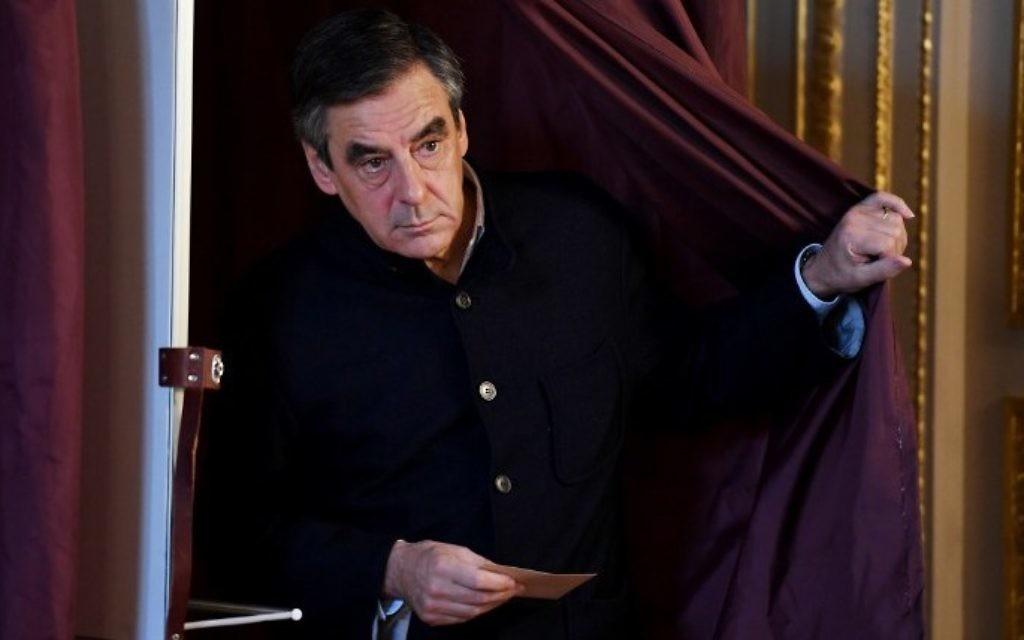 François Fillon, député français et candidat à la primaire de la droite et du centre pour les élections présidentielles françaises de 2017, sort de l'isoloir d'un bureau de vote de Paris, pour le second tour de l'élection, le 27 novembre 2016. (Crédit : Eric Feferberg/Pool/AFP)