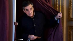 François Fillon, député français et candidat à la primaire de la droite et du centre pour les élections présidentielles françaises de 2017, sort de l'isoloir d'un bureau de vote de Paris, pour le second tour de l'élection, le 27 novembre 2016. (Crédit : AFP/Pool/Eric Feferberg)