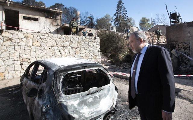Le ministre de la Défense Avigdor Liberman inspecte des maisons brûlées dans l'implantation de Halamish, en Cisjordanie, le 27 novembre 2016. (Crédit : AFP/Menahem Kahana)