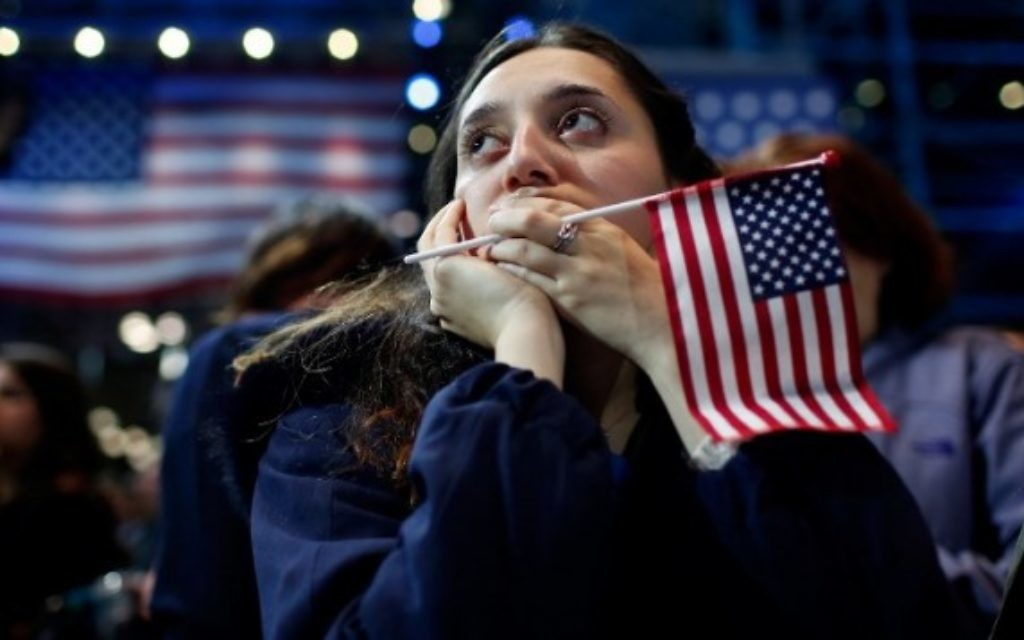 Une femme tient un drapeau américain alors qu'elle regarde les résultats du vote à l'élection présidentielle au Jacob K. Javits Convention Center à New York le 9 novembre 2016. (Crédit : Win McNamee / Getty Images / AFP)