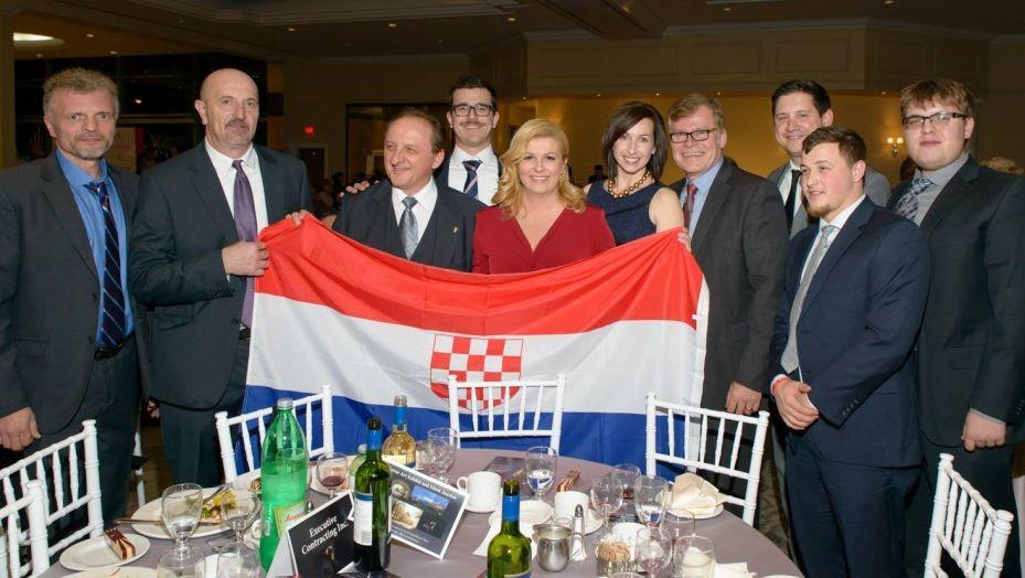 La présidente croate Kolinda Grabar-Kitarovic pose avec un drapeau portant le blason du régime croate pro-nazi de la Seconde Guerre mondiale, pendant un voyage au Canada en novembre 2016. (Crédit : Facebook)