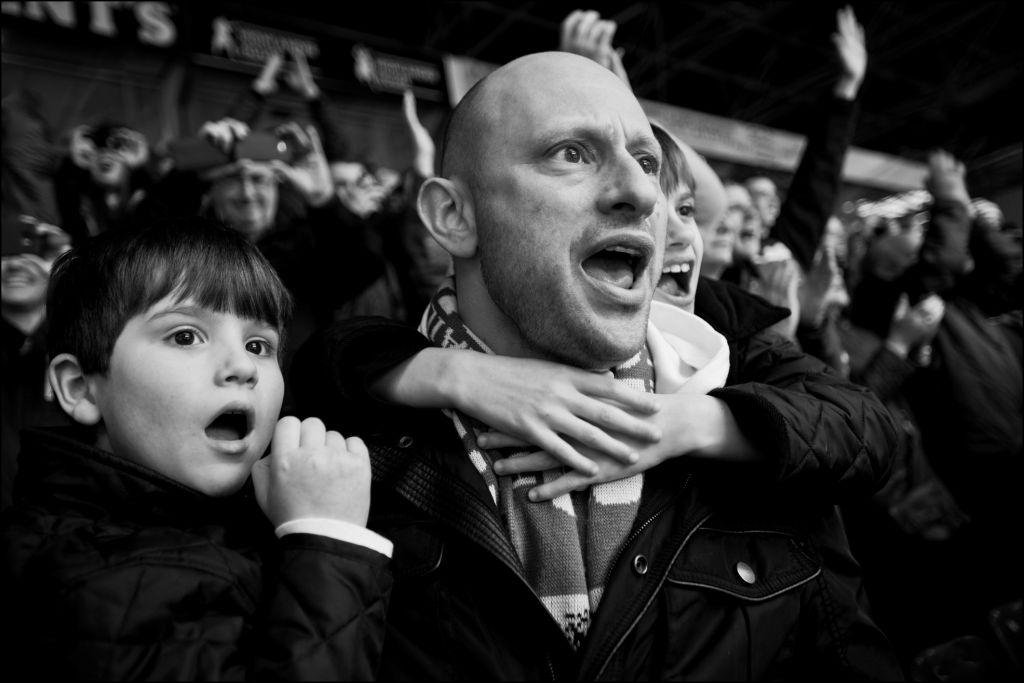 Un homme juif et son fils pendant un match de football. (Crédit : Judah Passow)