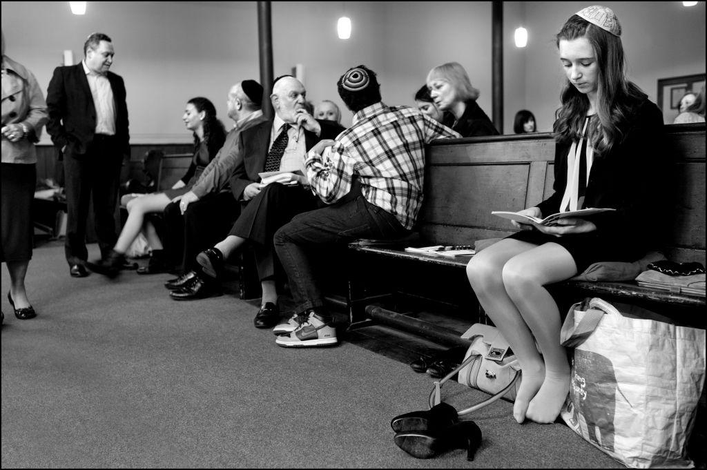 Des juifs écossais à la synagogue. Sur le côté, une jeune fille étudie son livre de prières alors que les autres fidèles se parlent. (Crédit : Judah Passow)